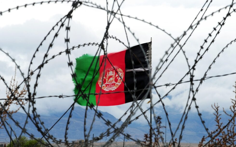 Afghan flag behind barbed wire.