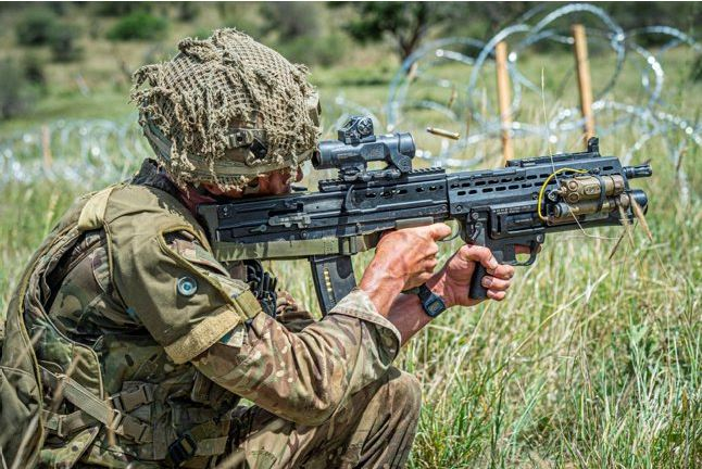 A British soldier fires his SA80-A3 with underslung grenade launcher during a live firing platoon level attack Exercise in Kenya.