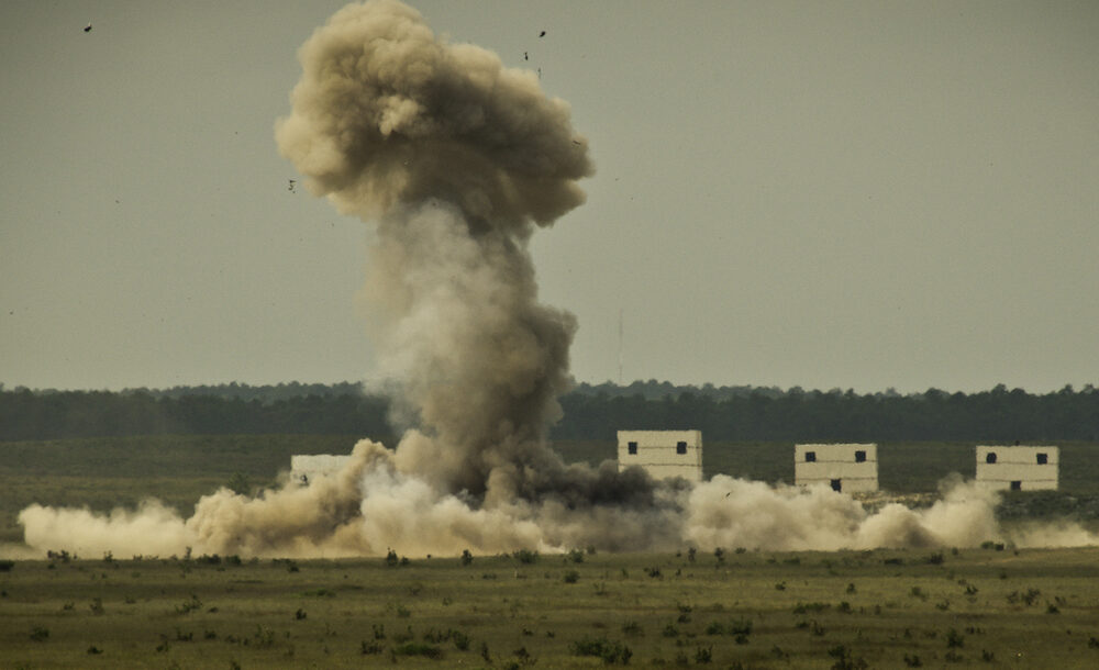 A cloud of heat and smoke erupts from the wreckage after a 1,500 pound explosive detonated in a controlled explosion on the Eglin Air Force Base range