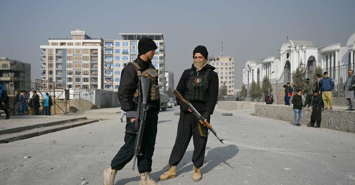 Policemen stand guard at the site of a bomb blast in Kabul on February 2, 2021.