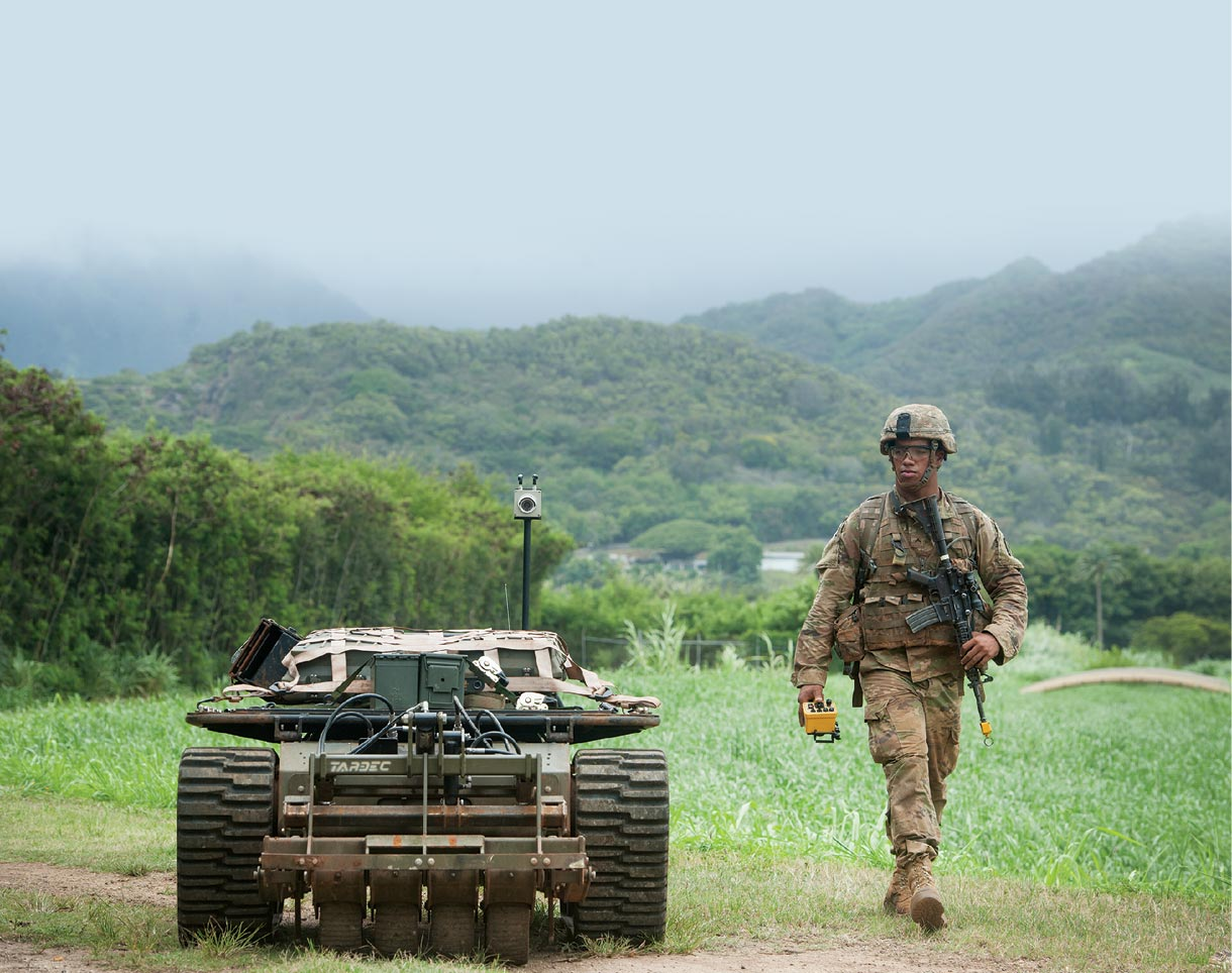 A US Army Pacific soldier walks down a trail 22 July 2016 while controlling an unmanned vehicle as part of the Pacific Manned Unmanned–Initiative at Marine Corps Training Area Bellows, Hawaii.