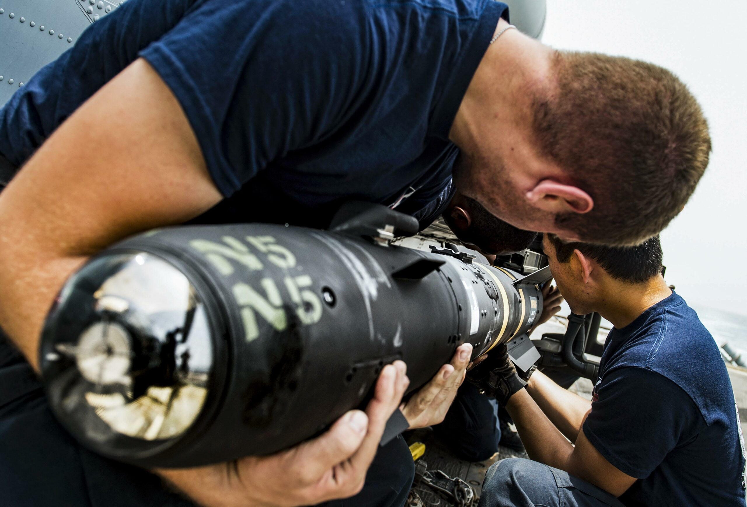 Sailors load an AGM-114 Hellfire missile onto an MH-60R Seahawk helicopter