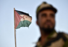 A Polisario Front soldier stands before a Sahrawi flag in Western Algeria