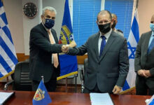 Israel Ministry of Defense official striking a pose concluding deal with Greek official