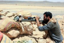 A fighter loyal to Yemen's government holds a position against Houthi rebels in Marib