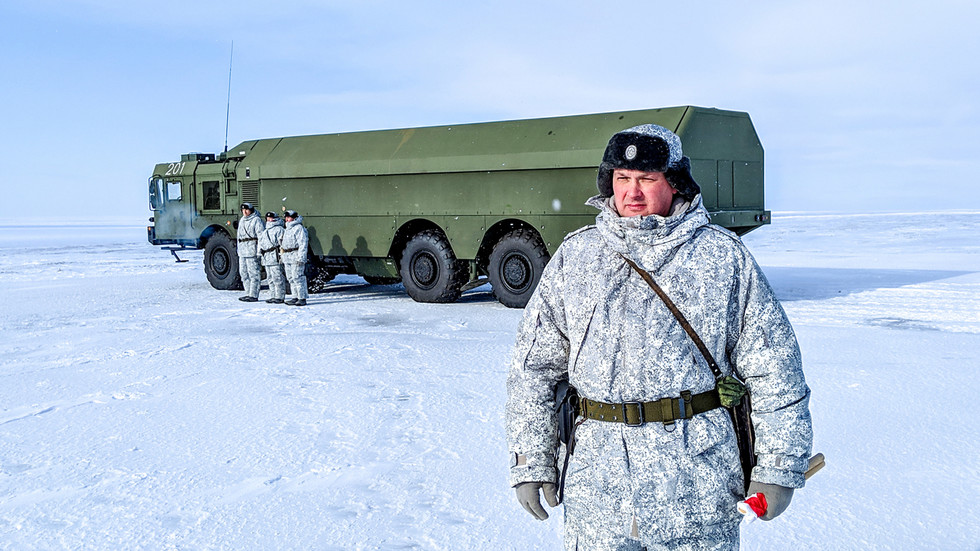 A Russian officer and soldiers stand next to a special military truck at the Russian northern military base on Kotelny island, beyond the Arctic Circle on April 3, 2019