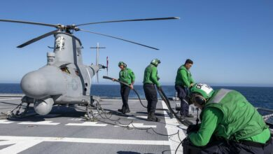 Sailors charge the battery of an MQ-8B Fire Scout unmanned aerial vehicle aboard Independence-variant littoral combat ship USS Charleston