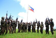 Philippine soldiers seen bannering the country's flag after killing almost 40 militants loyal to Islamic State groups