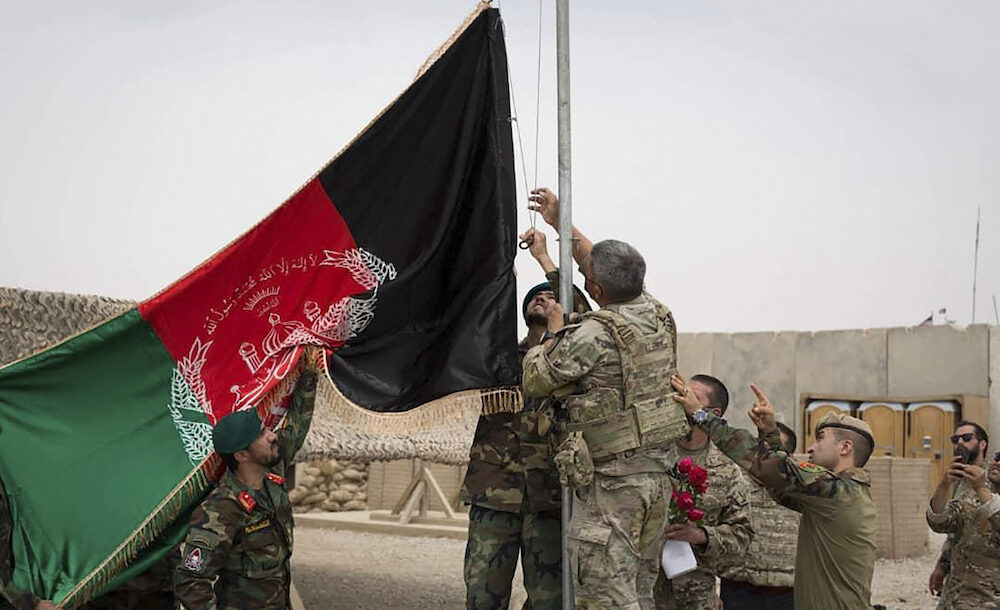 This handout photograph taken on May 2, 2021 and released by Afghanistan's Ministry of Defense shows US soldiwrs and Afghan National Army (ANA) soldiers rising Afghanistan's national flag uring a handover ceremony to the Afghan National Army (ANA) army 215 Maiwand corps at Antonik camp in Helmand province.