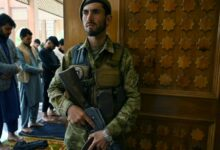 An Afghan soldier stands guard as Muslim devotees offer prayers to start the Eid-al-Fitr festival marking the end of the Islamic holy fasting month of Ramadan during a three-day ceasefire agreed by the warring Taliban and Afghan forces, at the Abdul Rahman Mosque in Kabul on May 13, 2021.