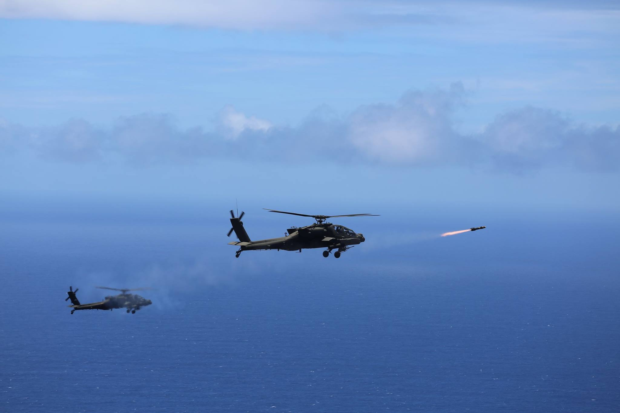 """Two US Army AH-64D Apache attack helicopters launch eight """"fire and forget"""" AGM-114L Hellfire Air to Surface Missiles during a training exercise off the coast of Oahu as part of the Rim of the Pacific in 2016."""