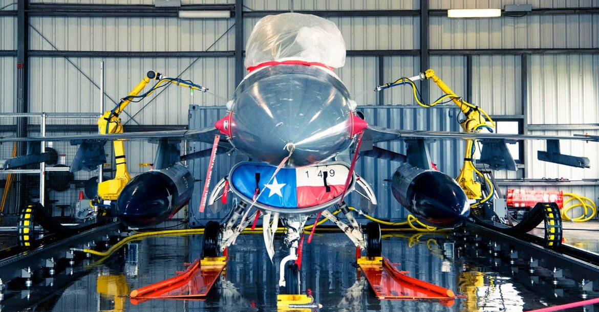 An F-16 fighter jet being washed by an automated cleaning system at Joint Base San Antonio-Lackland, Texas