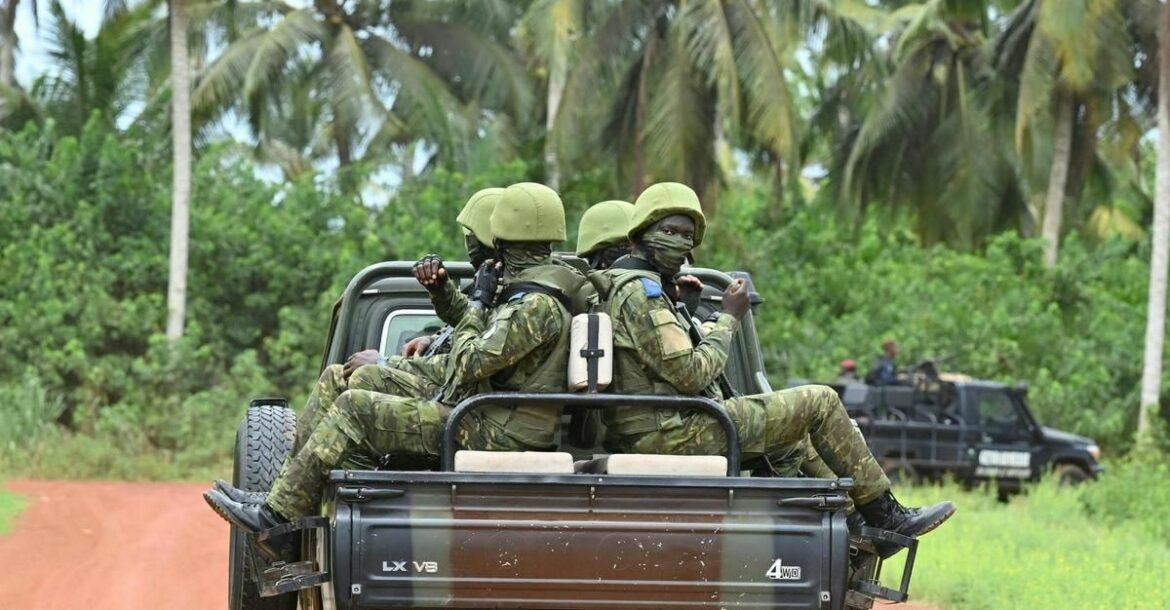 Ivorian soldiers drive on the back of a vehicle outside the International Academy for Combating Terrorism in Jacqueville in Ivory Coast on June 10, 2021