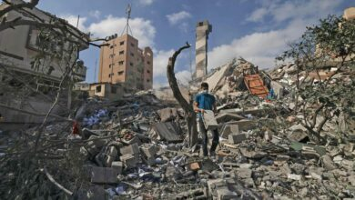 A Palestinian youth looks for salvageable items amid the rubble of the Kuhail building, which was destroyed in an early morning Israeli airstrike on Gaza City