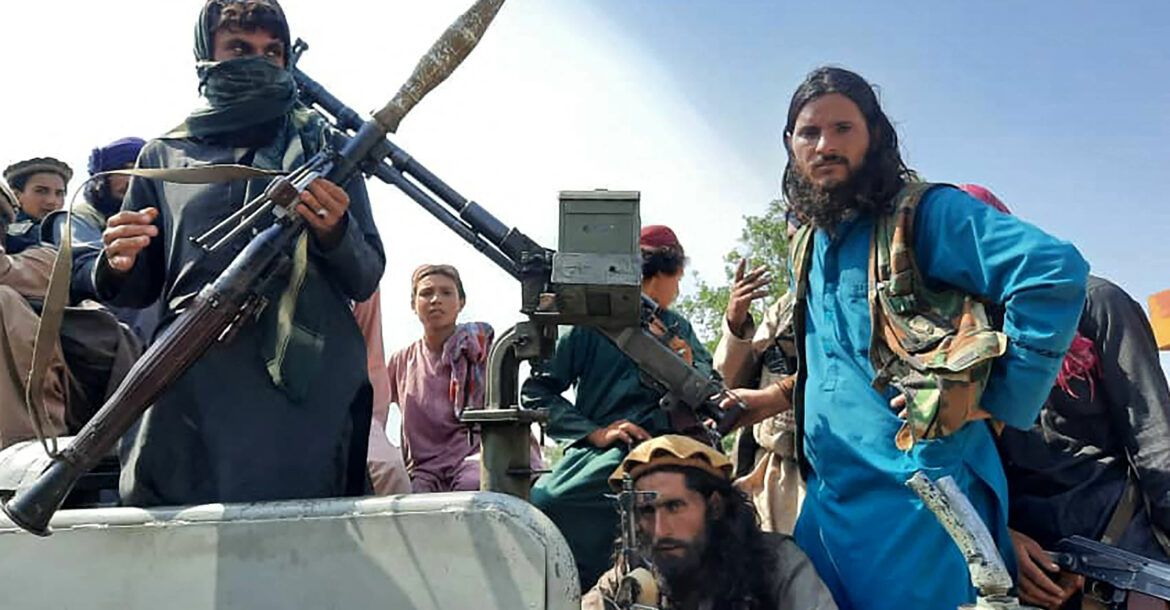 Taliban fighters sit over a vehicle on a street in Laghman province