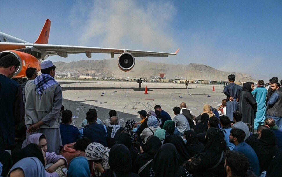 Afghan people wait to leave the Kabul airport on August 16, 2021