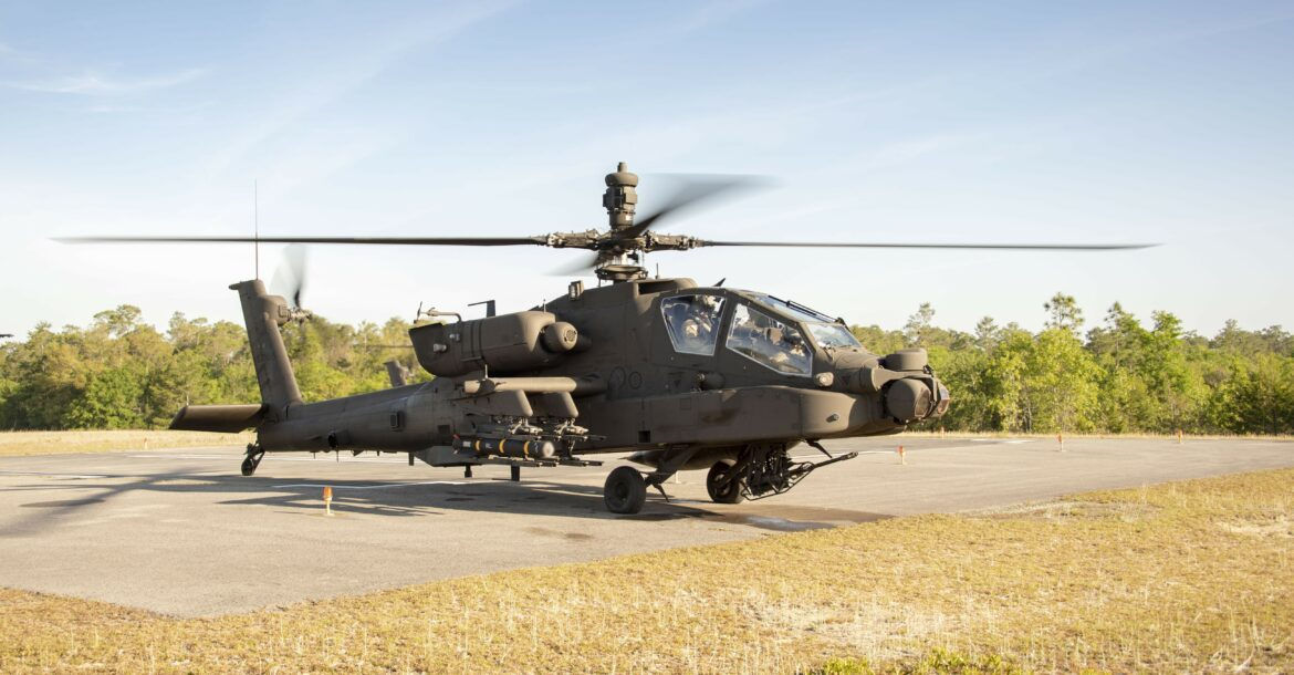 A Joint Air to Ground Missile (JAGM) is loaded onto an AH64E Apache Attack Helicopter