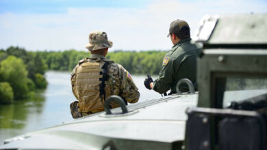 A Texas Guardsmen and a Customs and Border Patrol agent discuss the lay of the land on the shores of the Rio Grande River in Starr County, Texas.