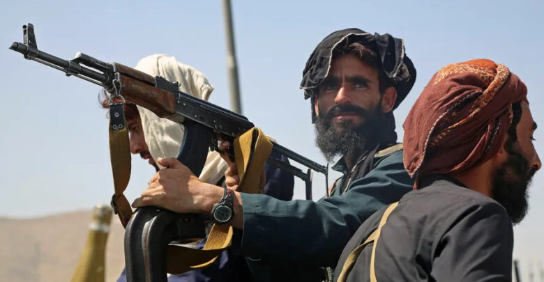 Taliban fighters stand guard in a vehicle along the roadside in Kabul on August 16, 2021