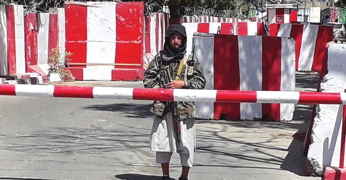 A Taliban fighter stands guard at the entrance of the police headquarters in Ghazni on August 12, 2021