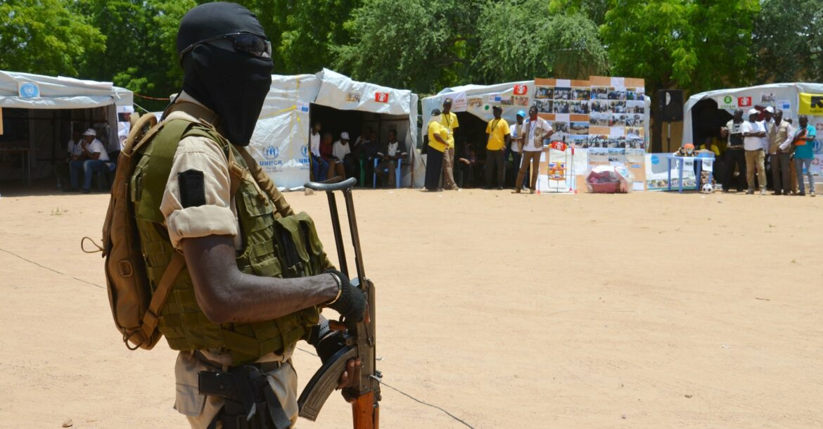 A soldier stands guard near information stands in a camp in Diffa, Niger