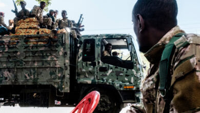 Members of the Amhara Special Forces seat on the top of a truck while another member looks on in the city of Alamata, Ethiopia, on December 11, 2020
