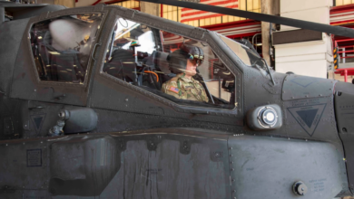A US Army pilot observes the features of an enhanced Helmet Mounted Display from the front seat of an AH-64E Apache Helicopter