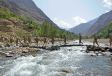 Anti-Taliban fighters crossing a river in the Panjshir valley
