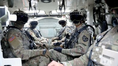 American soldiers wearing the Integrated Visual Augmentation System (IVAS) goggles while inside a Stryker.