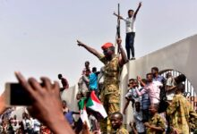 After Sudanese President Omar al-Bashir was ousted, members of the Sudanese military gather in a street with protestors in central Khartoum