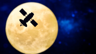 A satellite silhouette in front of a full moon